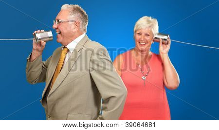 Senior Couple Having A Chat With A Tin On Blue Background