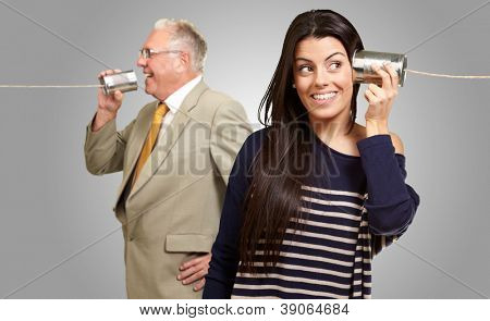 Senior Man Talking With Young Woman On Tin Can On Gray Background