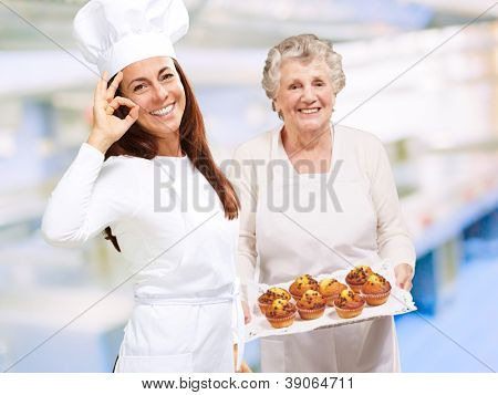 Two Happy Female Chef Presenting Muffins, Indoor