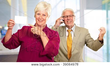Businesswoman Showing Card In Front Of Man Using Cell Phone, Indoors