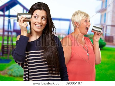Two Happy Woman Talking On Tin Can, Outdoor