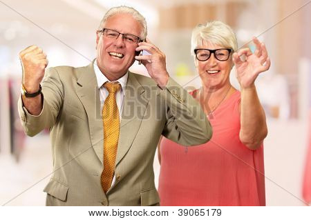 Man Taking On Cellphone In Front Of Woman, Indoor