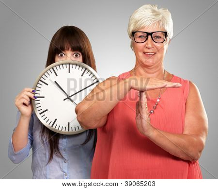 Senior Woman Showing Timeout Sign In Front Of Young Woman Holding Clock On Gray Background