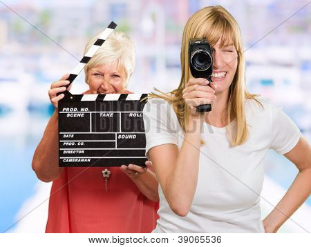 Two Happy Woman Holding Clapper Board And Camera, Outdoor