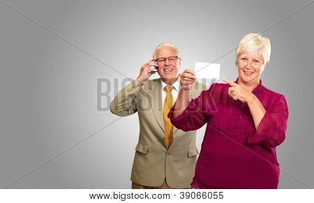 Businesswoman Showing Card In Front Of Man Using Cell Phone On Gray Background