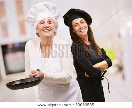 Senior Chef Holding Pan In Front Of Smiling Woman, Indoor