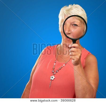 Senior Woman Looking Through A Magnifying Blue On blue Background