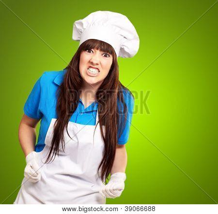 Retrato de un mujer chef apretamiento en fondo verde