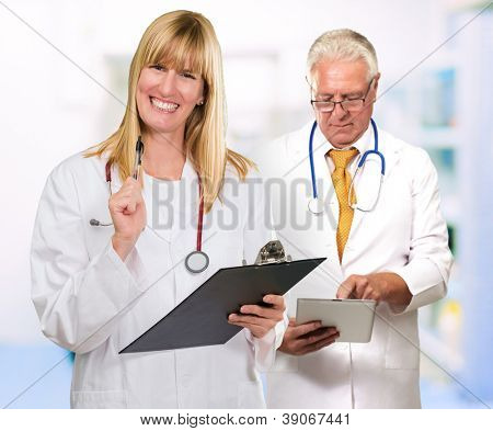 Two Happy Doctors While Holding Clipboard And Tablet, Indoors