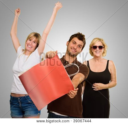 Man Holding Shopping Bag In Front Of Two Happy Women On Gray Background