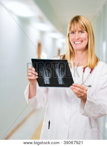 Portrait Of Happy Doctor Holding X-ray in a passageway