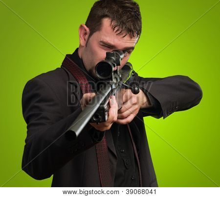 Man in suit pointing with a rifle against a green background