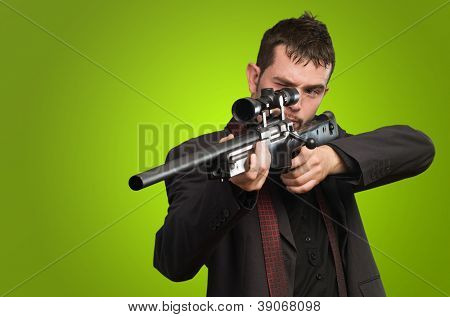 Young Man Aiming With Rifle against a green background