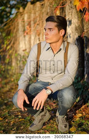 Handsome young man  in fall (autumn) in front of wood fence