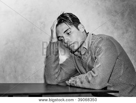 Attractive young man holding his head, sad or worried