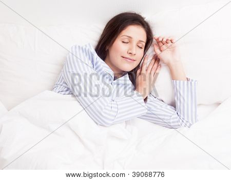 young brunette woman wearing pajamas on the white linen in bed at home, top view