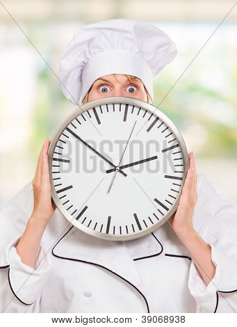 worried chef hiding behind a clock, outdoor