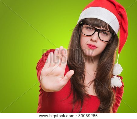 christmas woman doing a stop gesture against a green background