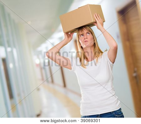 woman holding a box on her head in a passage way