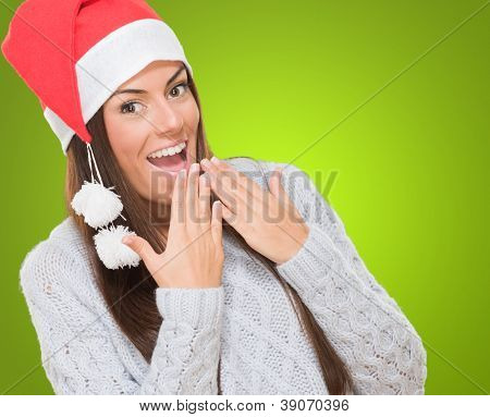 Excited woman wearing a christmas hat against a green background