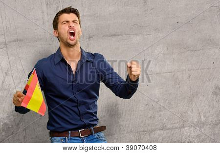 Man cheering and holding flag, indoor