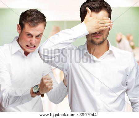 Jovem homem cobrindo os olhos e agressivo homem de pé atrás, dentro de casa