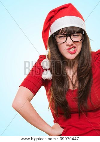 angry christmas woman wearing glasses against a blue background