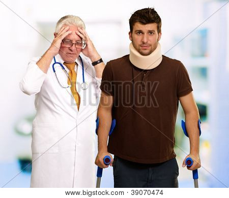 Young Man Wearing Cervical Collar And Frustrated Doctor Behind It, Indoors