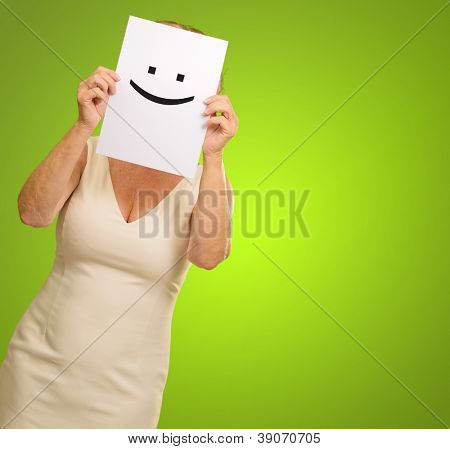 mature woman holding smile sign isolated on green background