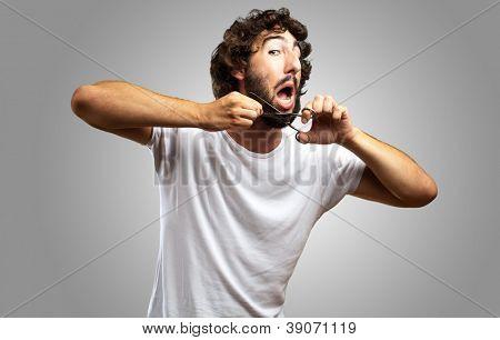Man Cutting Beard against a grey background