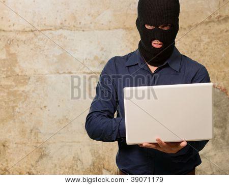 Junge männliche Dieb holding Laptop, im freien