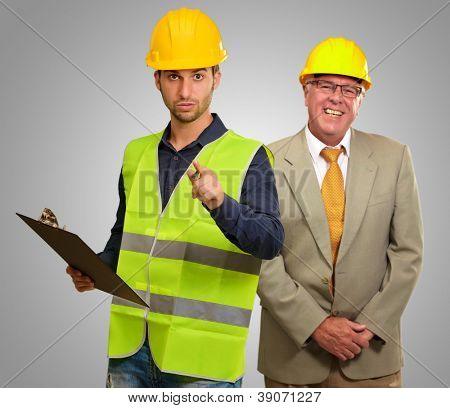 Portrait Of Two Architect Engineers On Gray Background