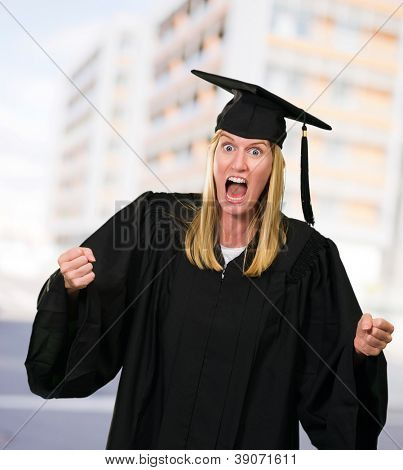 Portrait of an angry graduate against a building as a background, outdoor