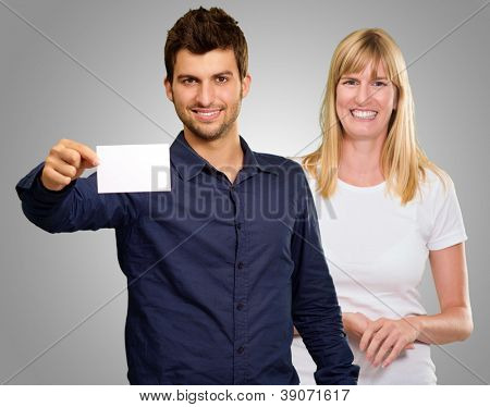 Man Hand Holding Blank Placard And Happy Woman Standing Behind On Gray Background