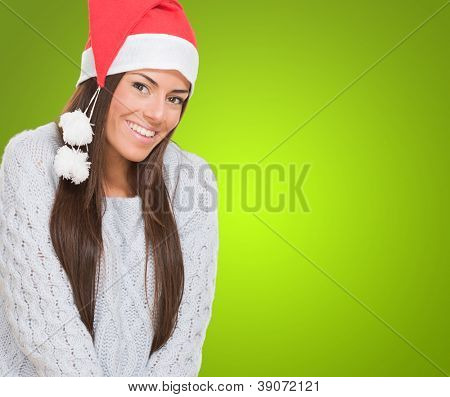 Beautiful woman wearing a christmas hat against a green background