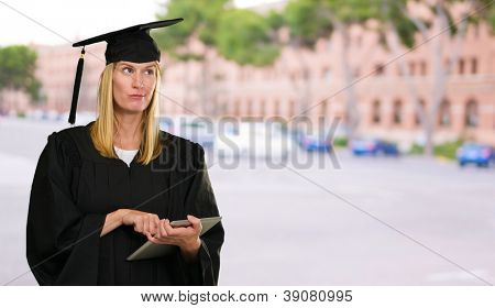 Confused Graduate Woman Holding Digital Tablet against a unversity building as a background