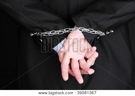 Businessman hands fettered with chain