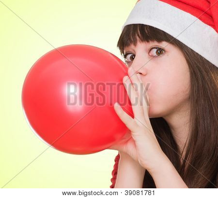 woman wearing a christmas hat and blowing a balloon against a yellow background