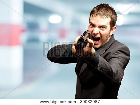 Angry Man Holding Gun in a garage