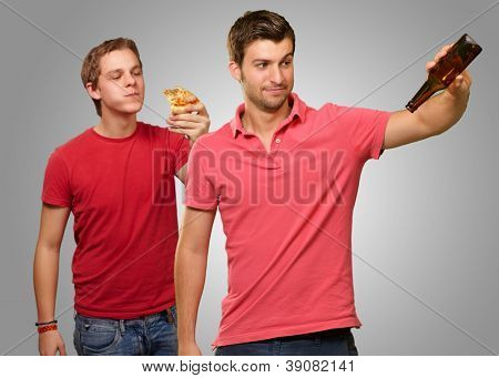 Young Man Holding Empty Bottle And Other Man Having Pizza On Gray Background