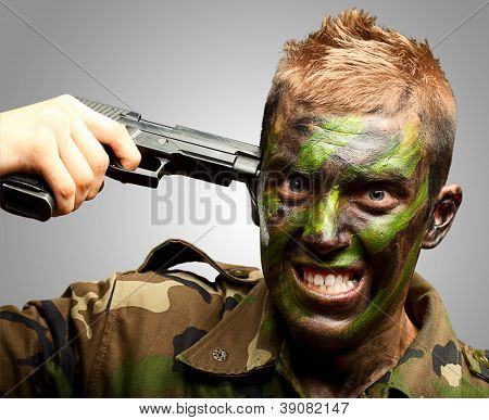 Soldier Putting Gunshot On Head against a grey background