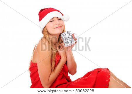 A portrait of a sexy woman in Santa's hat wrapped in a red blanket and holding a mug of hot drink over white background
