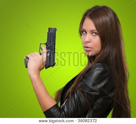 Portrait Of A Woman Holding Gun against a green background