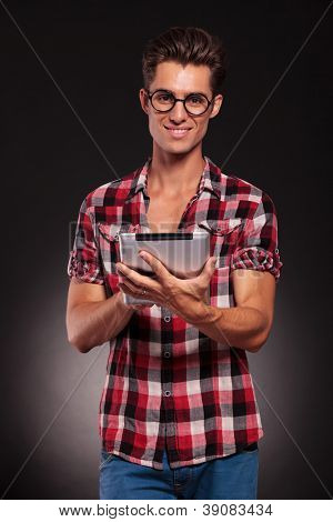 happy young casual man wearing glasses working on a touchscreen tablet