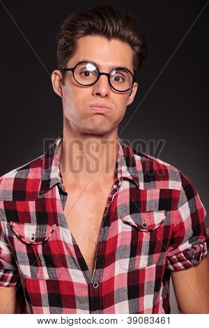 young casual man with funny face and wearing glasses on black background
