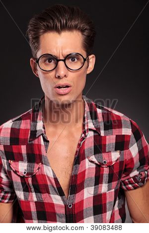young casual man wearing glasses  looking very shocked on a black background