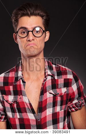 Portrait of ignorant casual man wearing glasses on black studio background