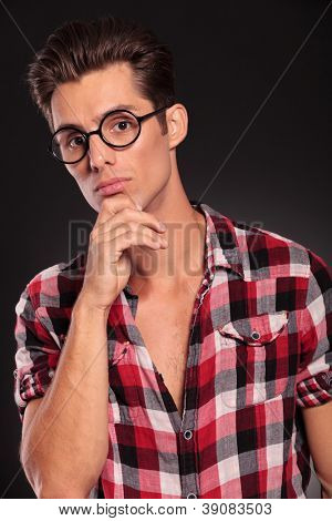 Closeup portrait of thoughtful young man in glasses against white background