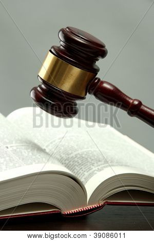 wooden gavel and book on wooden table, on grey background