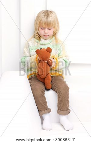 Little Girl 3 years with a brown teddy bear sitting on a white sofa